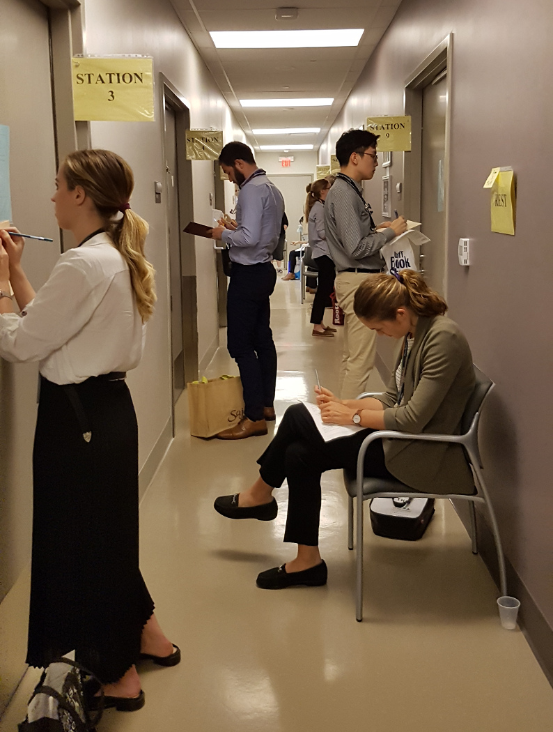 Evaluators standing outside exam rooms waiting to enter